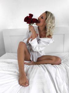 šopek rdečih vrtnic v postelji