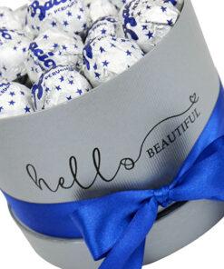 bacio je primerno darilo za moškega in je v sivi škatli z modro pentljo in čokoladicami bacio