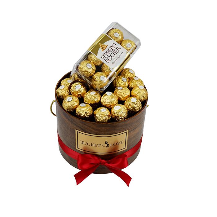 ferrero roche čokoladice v rjavem lesenem vrču z rdečo penetljo in zlatim napisom