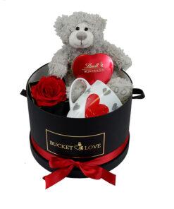 siv plišasti medvedek z rdečim srcem in rdečo kraljevo vrtnico in šalčko s srčkom