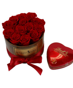 red lindt heart with chocolates besides wooden bucket of love with res roses