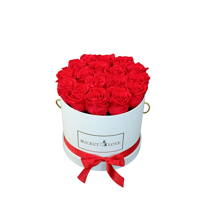 golden text on a white bucket filled with flowers on a white background
