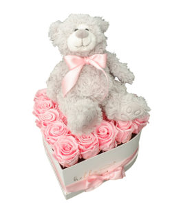 siv plišasti medvedek z roza pentljo sedi na roza rožah v sivi srčkasti škatli