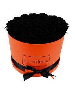 elegantne črne preparirane vrtnice v oranžni okrogli škatli