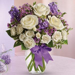 šopek cvetja igrivost je sestavljen iz belih vrtnic, zelenja in vijoličnega cvetja