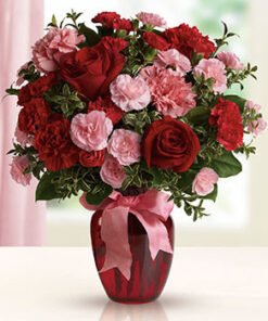 šopek iz ljubezni je sestavljen iz rdečih vrrtnic zelenja in roza barve cvetja